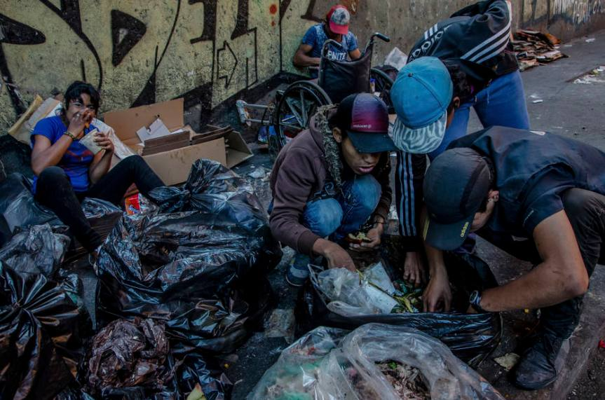 Families salvage food scraps from garbage bags in downtown Caracas, Venezuela.